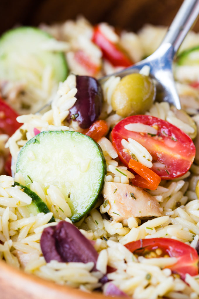 greek chicken orzo pasta salad in a bowl with spoon. Close up.