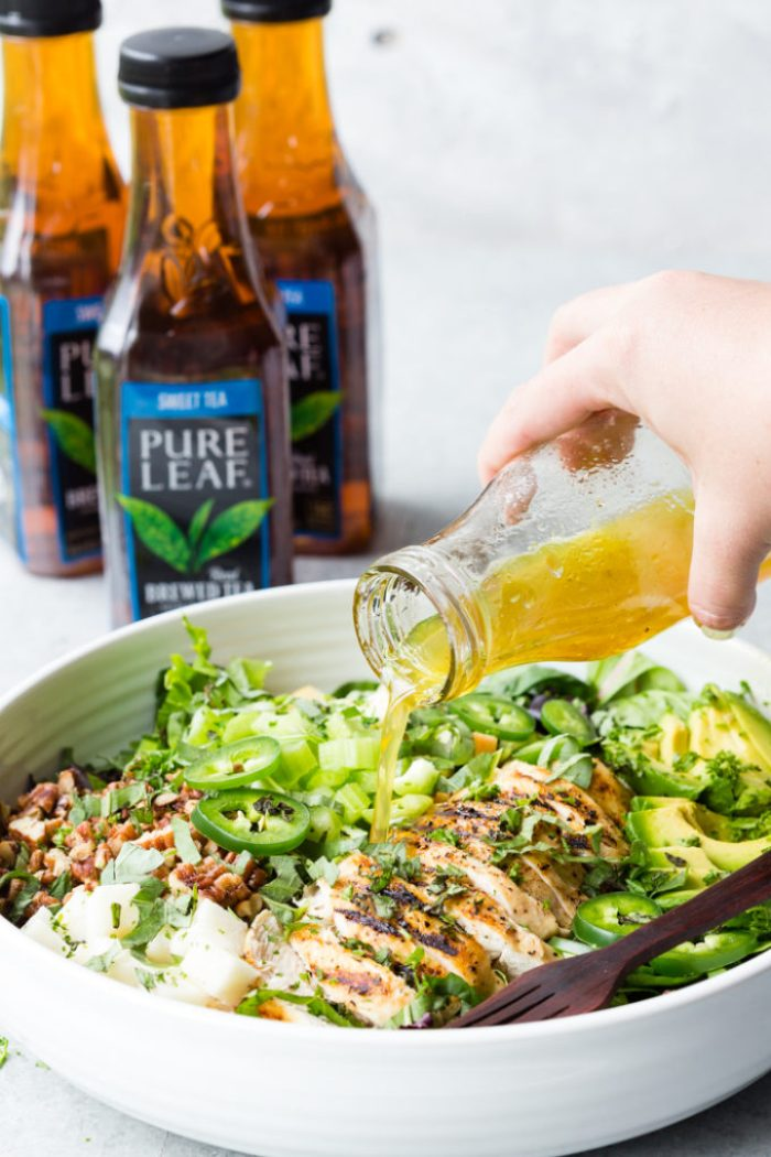 A white bowl full of grilled chicken salad and a hand pouring a dressing over top.