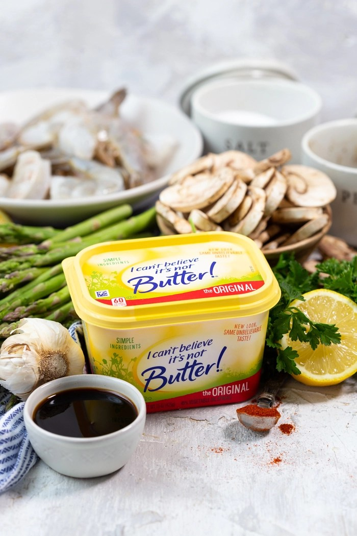 Ingredients needed for a low calorie sheet pan dinner of shrimp and asparagus and mushrooms with a honey lemon garlic sauce