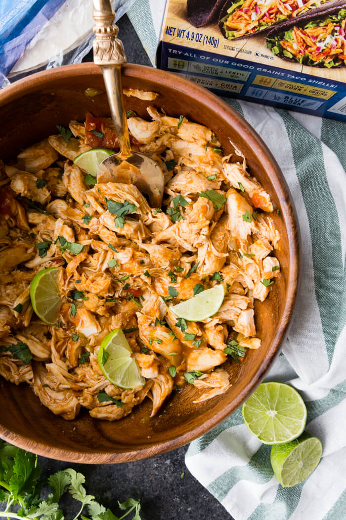 Shredded Chicken made in a pressure cooker served in a wooden bowl with a metal spoon with limes and parsley as garnish
