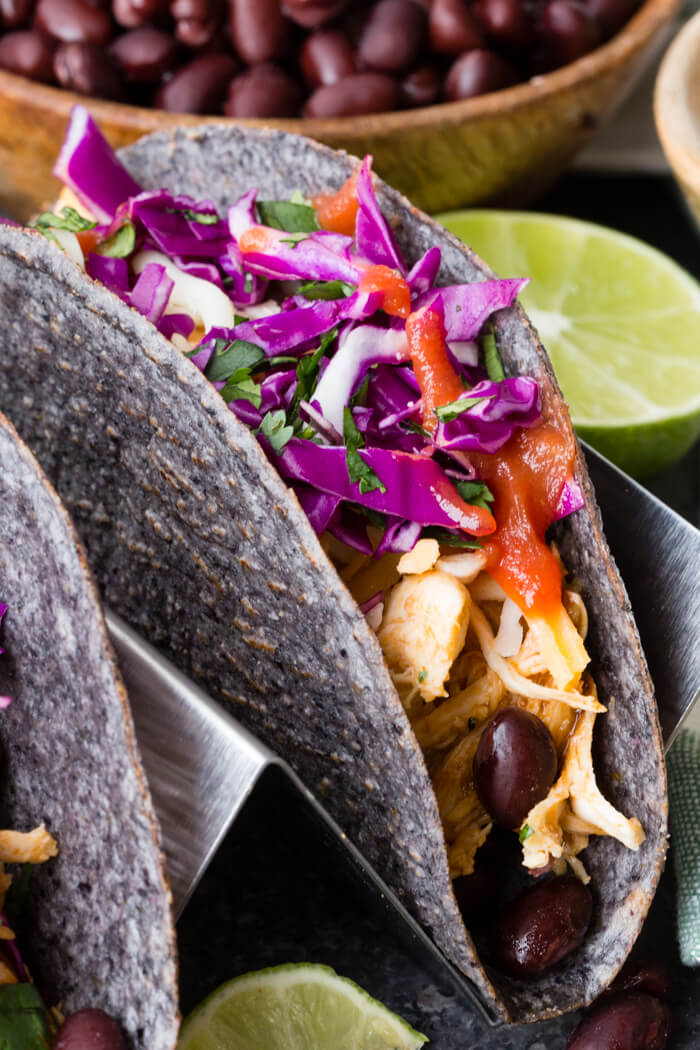 a blue corn taco shell filled with slow cooker Mexican shredded chicken, black beans, and veggies in a metal taco holder