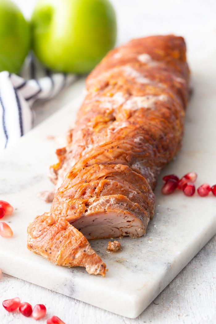 A roasted pork tenderloin on a marble cutting board