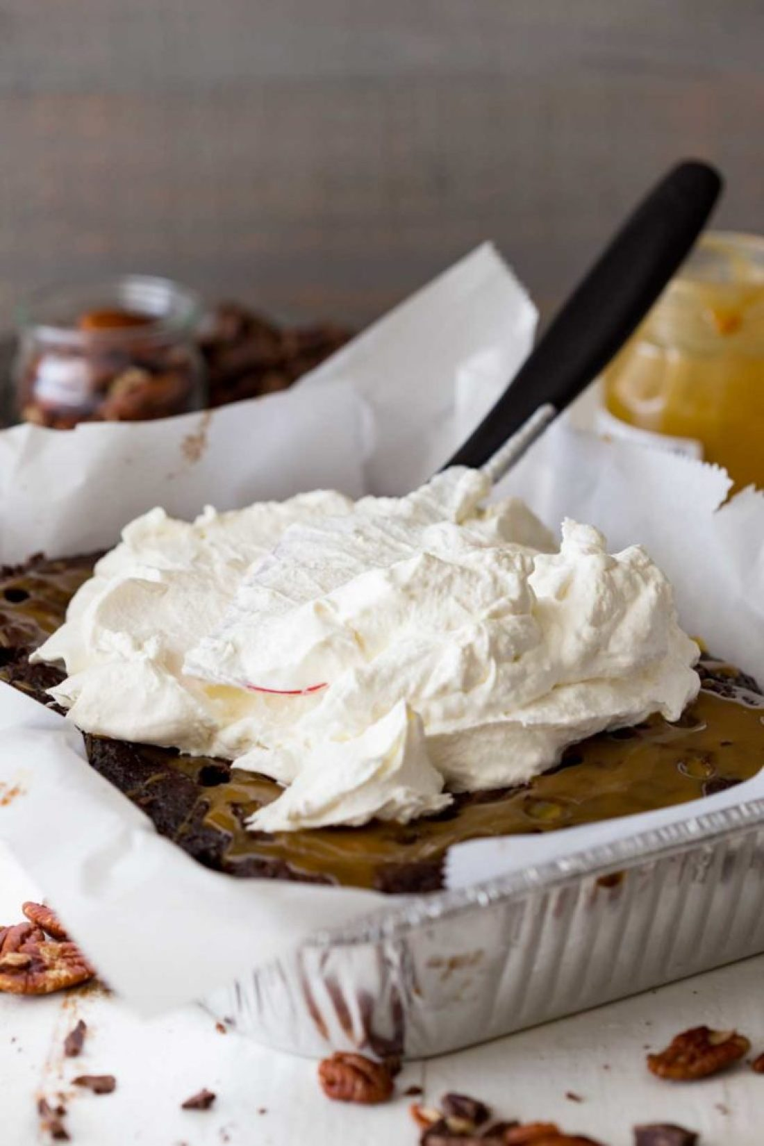Spreading whipped cream over the easy turtle poke cake!