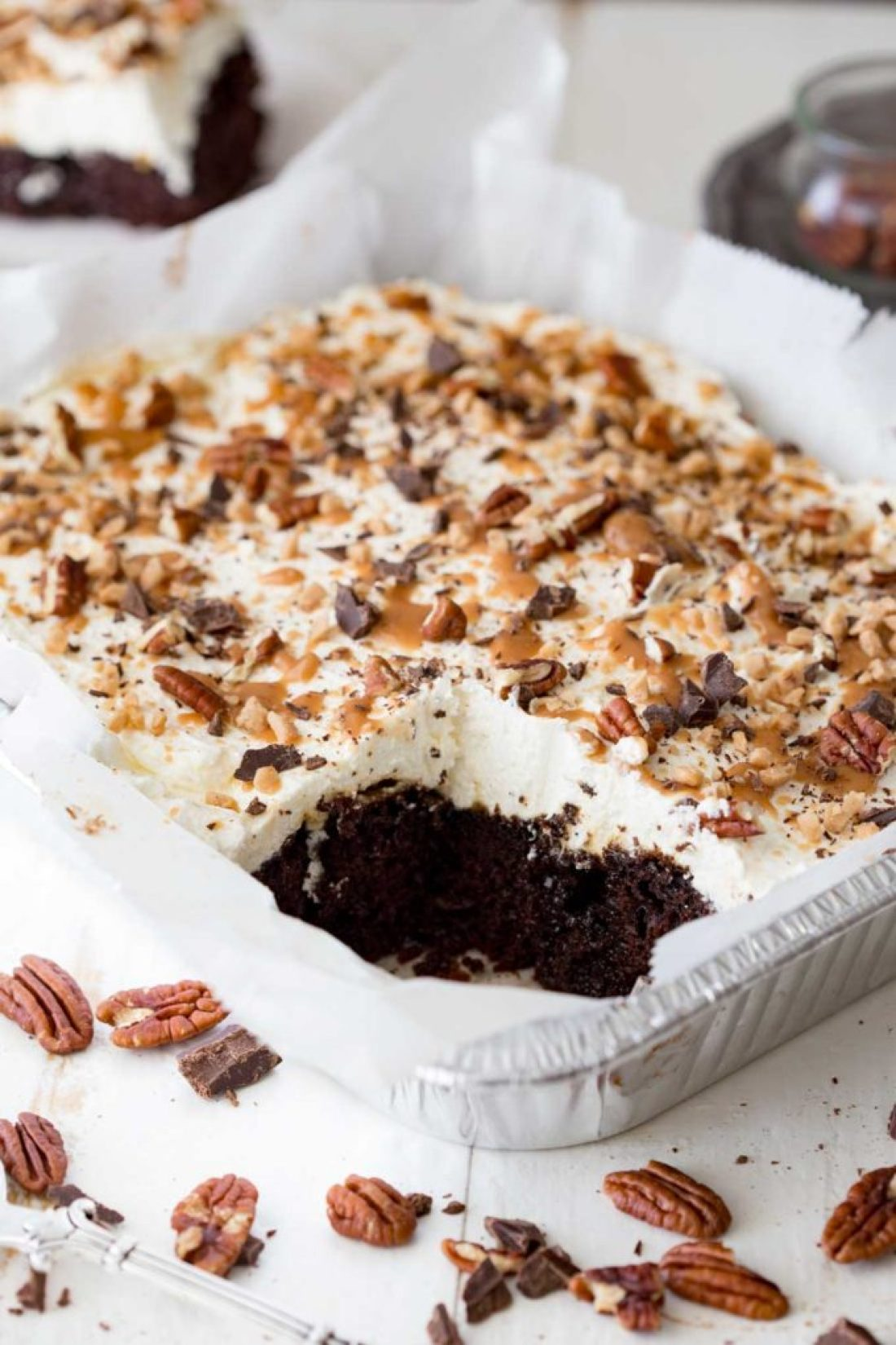 A rich decadent and unique turtle poke cake that is easy to make and topped with toffee as well as caramel, chocolate, and pecans