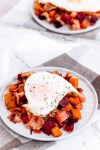 Bacon and Eggs Veggie hash on a white plate topped with an egg