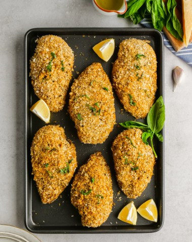 Breaded Chicken lying on cooking sheet, with lemons and herbs.