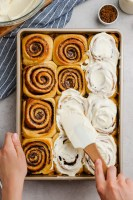 The best gooey, delicious, cinnamon rolls, top down shot, spreading cream cheese icing over the top.