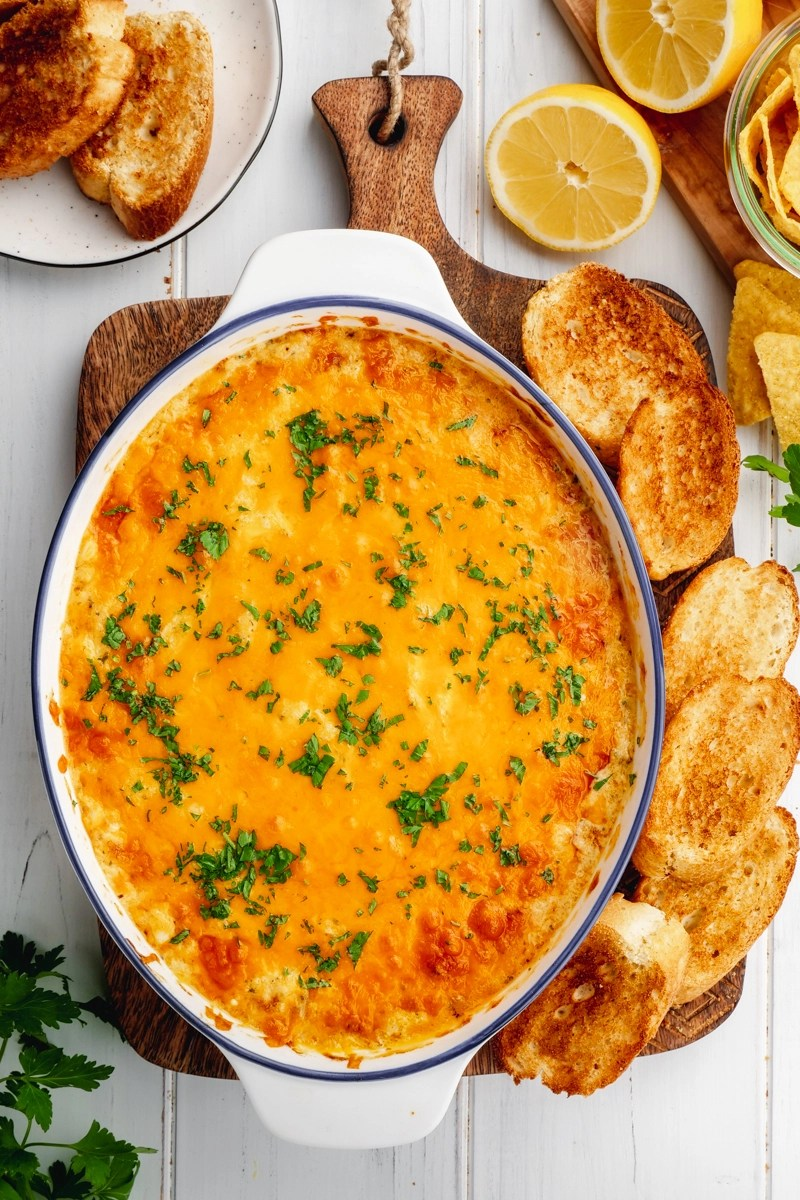 A casserole dish with crab dip, and dippers around it.