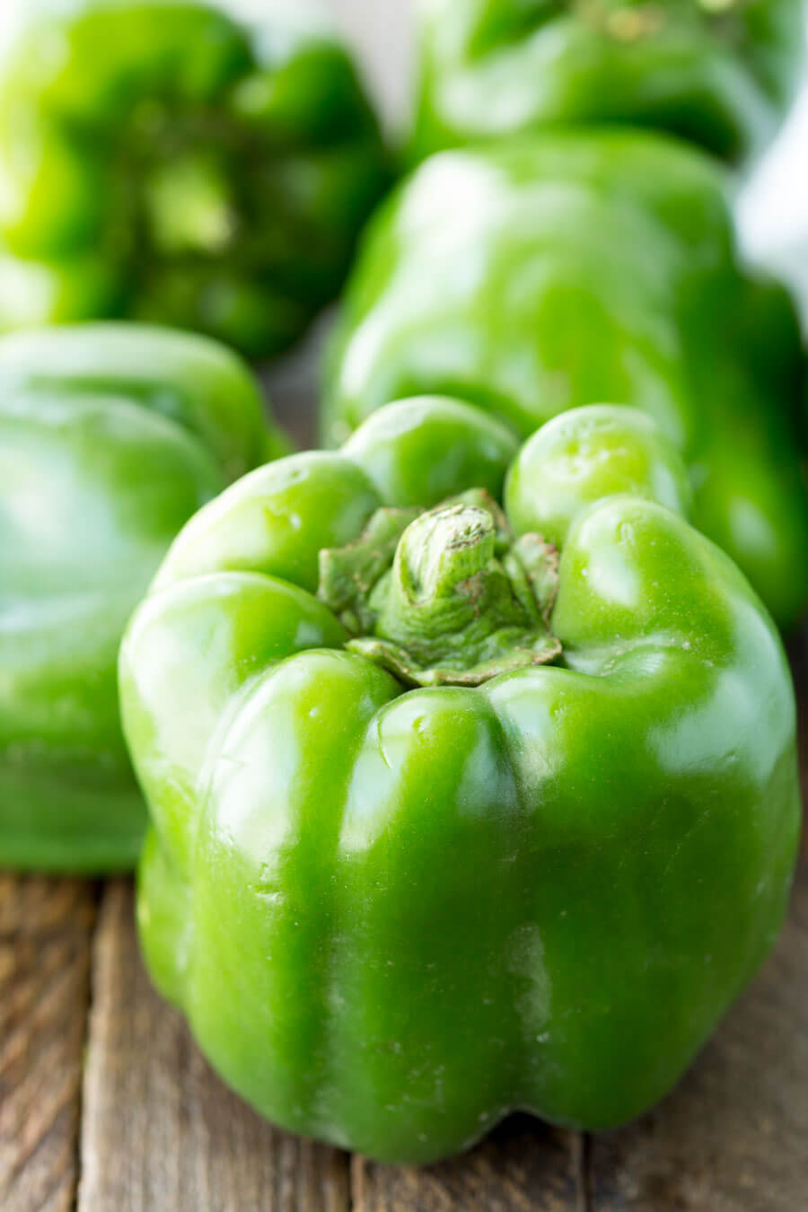 whole green bell peppers on a wooden surface