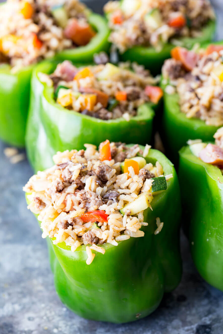 Green bell peppers stuffed with rice, sausage, and vegetables ready to be baked or frozen, sitting on a gray table