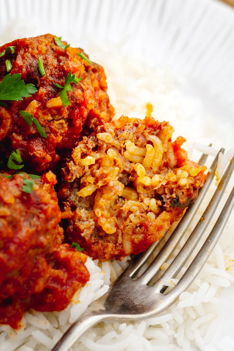 Porcupine meatballs, rice and sauce with a homemade meatball, and fork on the side.