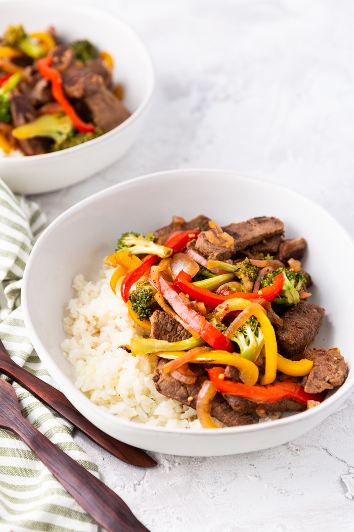 furthest away view of the steak stir fry in a bowl with another bowl behind