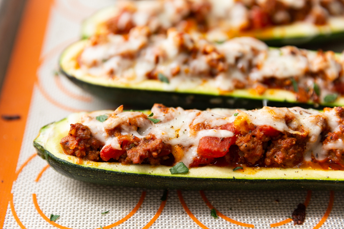 Zucchini boats stuffed with ground beef and tomatoes, topped with mozzarella and fresh herbs.