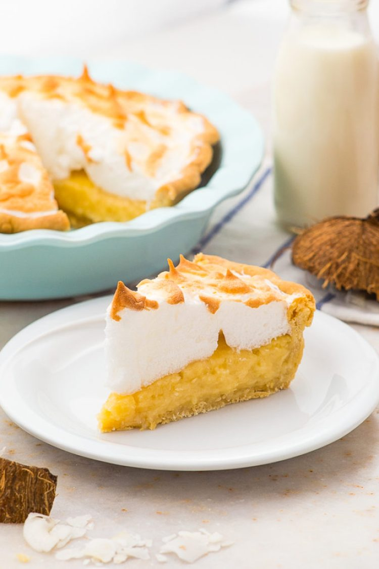 Thick and creamy coconut cream pie topped with fluffy meringue with milk and coconut shells in the background