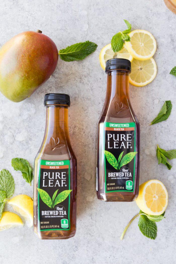 2 bottles of pure leaf black tea, with mangos, and lemon slices around them for making mango black tea lemonade