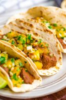 Three tacos al pastor with pineapple pico on top and lime garnish