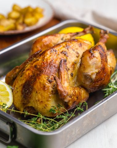 Beautifully roasted chicken, oven roast chicken in a pan with lemons and rosemary