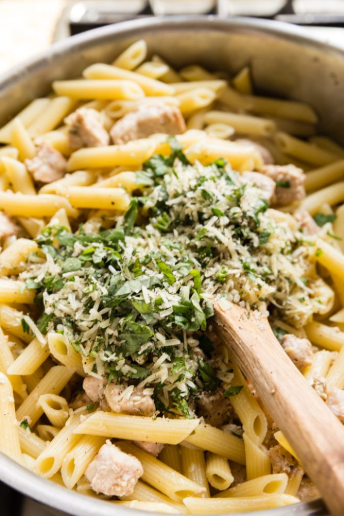 A pot of penne pasta with a pile of herbs and seasonings on top ready to be mixed in with a wooden spoon