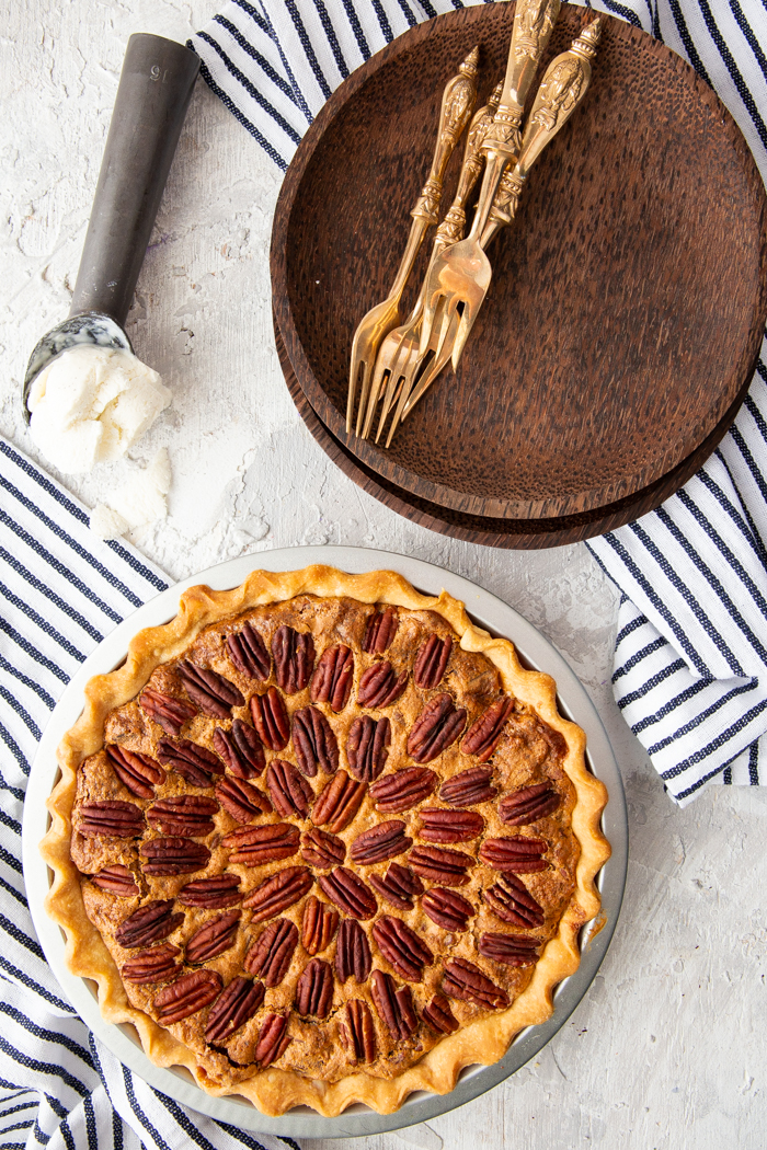 Pecan Pie recipe with a whole pie, brown plates, gold forks, and ice cream