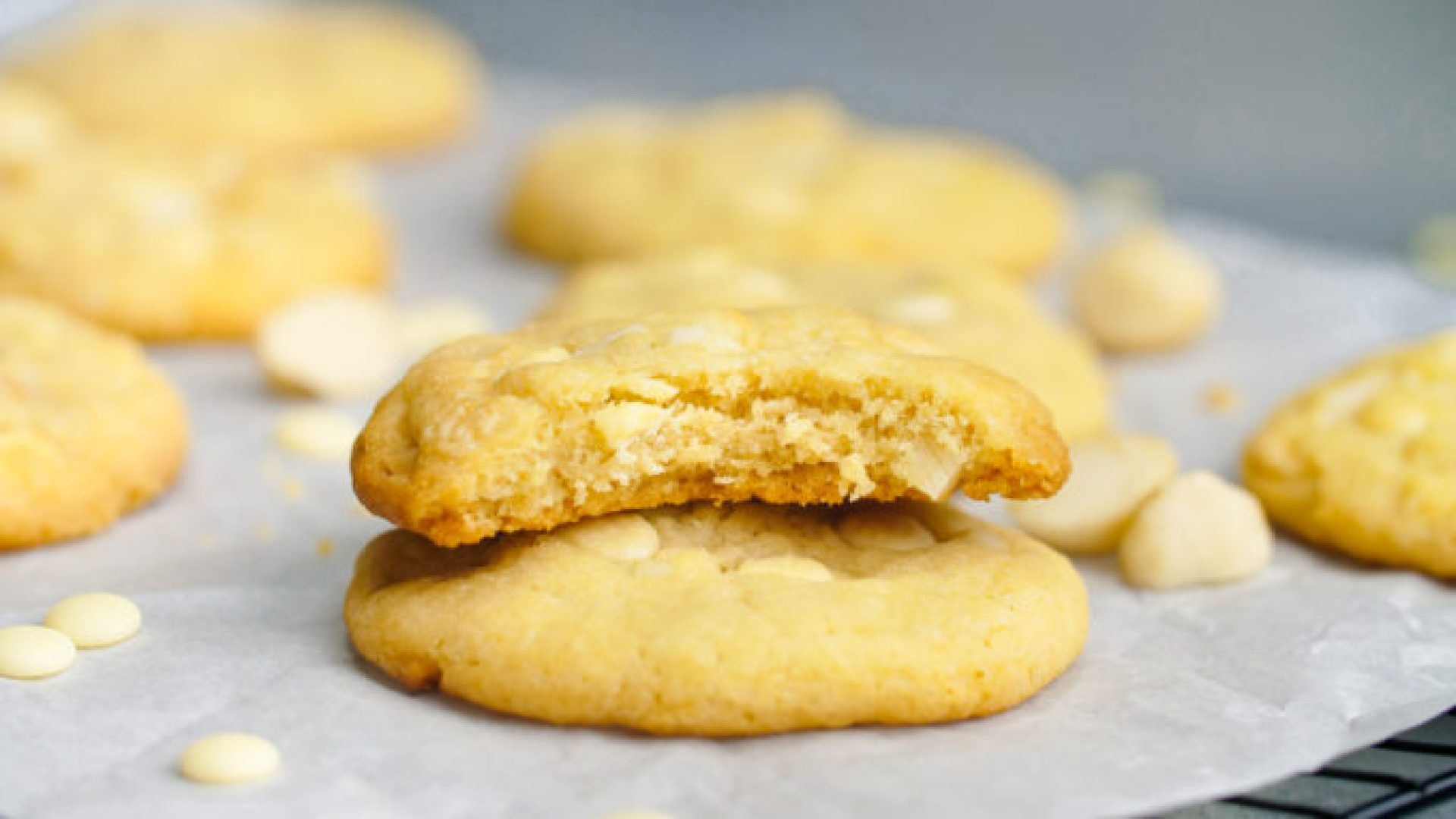 A delicious white chocolate macadamia nut cookie with a bite out, sitting a top another white chocolate chip macadamia nut cookie with a few cookies in the background
