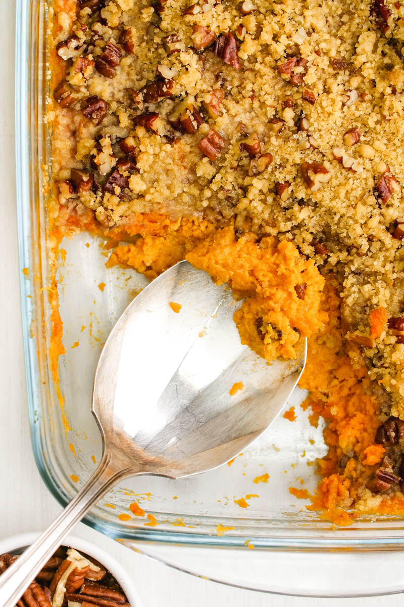 Sweet Potato Casserole in a baking pan with a serving spoon