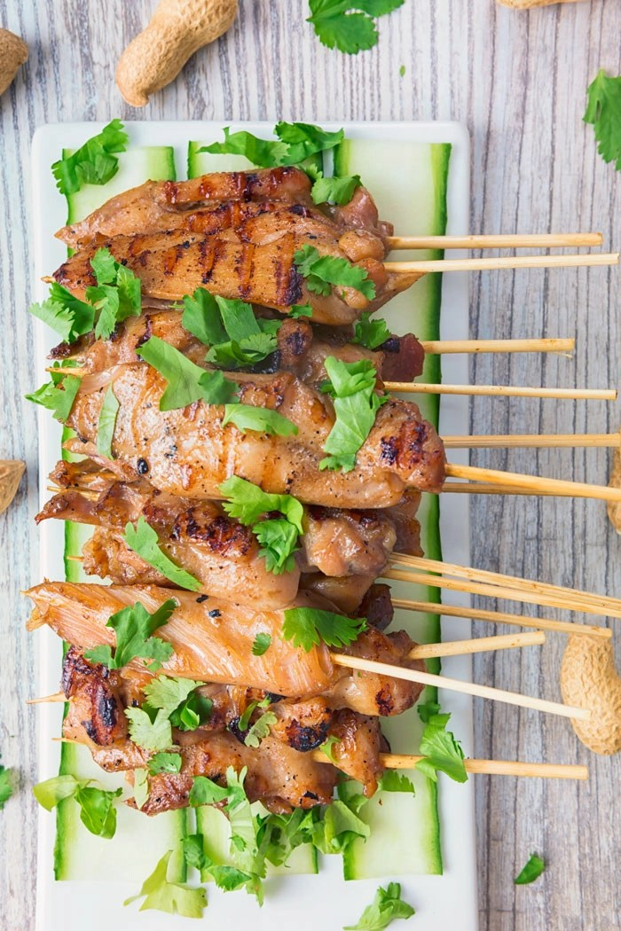 A white plate with several skewers of chicken satay