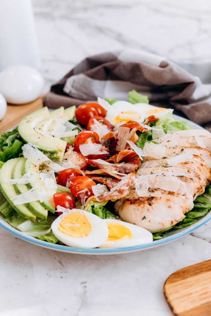 A plate of chicken avocado caesar salad, with a napkin behind and some boiled eggs
