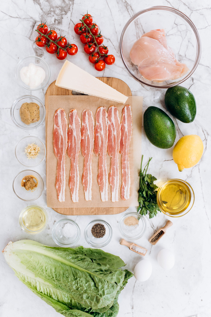 All the ingredients needed for a chicken avocado caesar salad, bacon, lettuce, avocado, lemon, chicken tomatoes, all on a marble surface