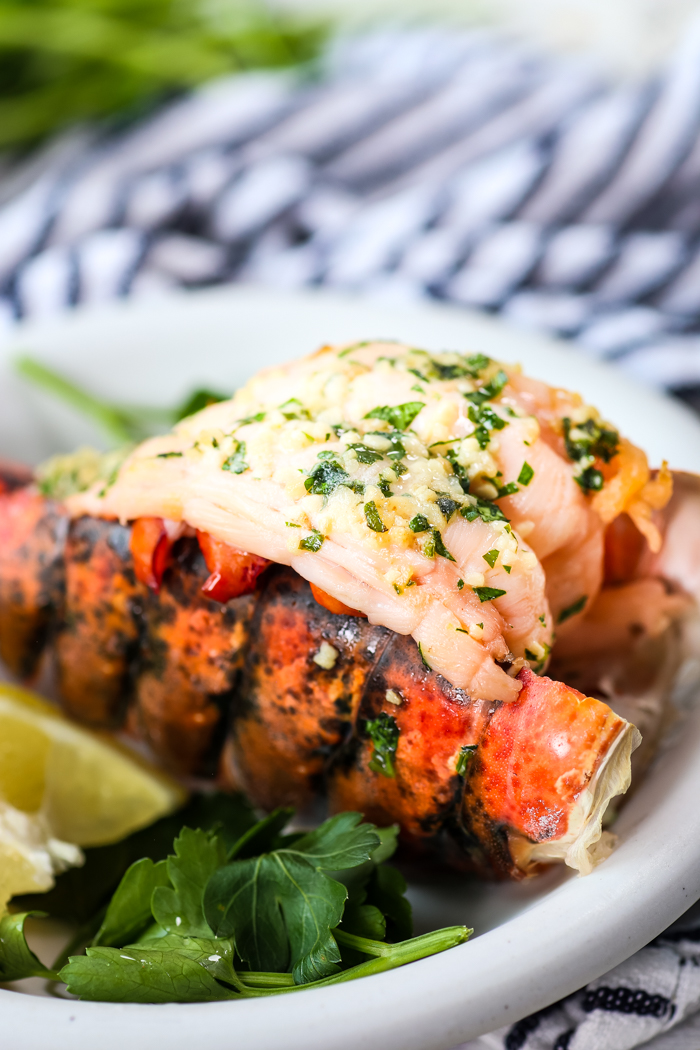 Instant Pot Cooked Lobster topped with butter and parsley and garlic