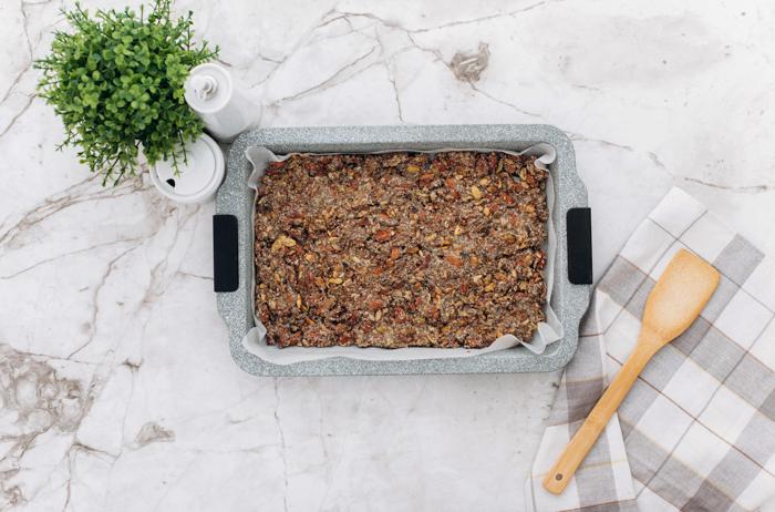 baking dish filled with keto granola and wood spatula
