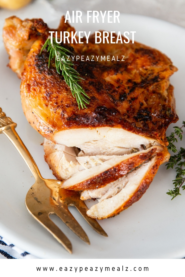Air fryer turkey breast on a white plate, with a few slices, and a gold serving fork