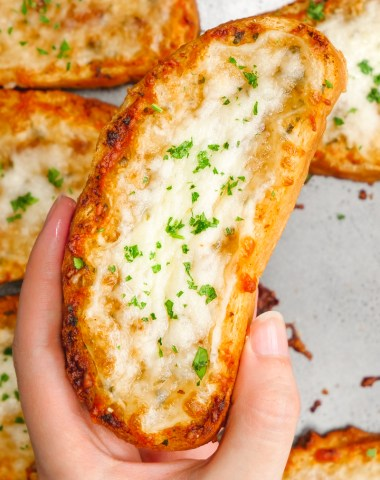 A lovely slice of cheesy garlic bread in a hand over a sheet of garlic bread