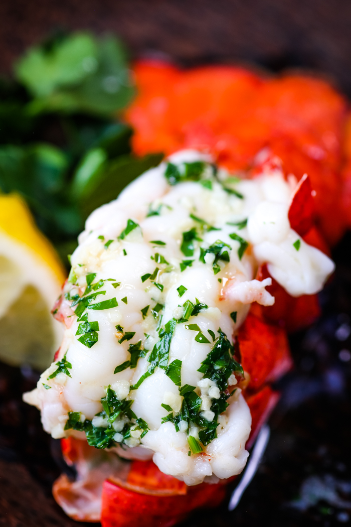 Boiled lobster tail topped with garlic butter and parsley