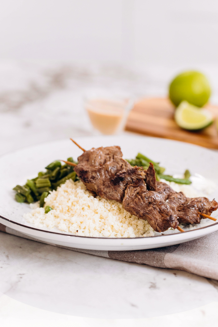 a plate with two skewers of beef satay with peanut sauce and limes