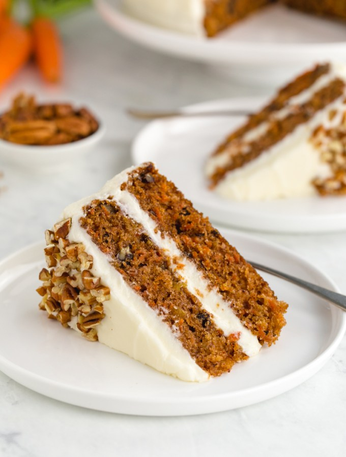 A slice of carrot cake with cream cheese frosting, two layer cake