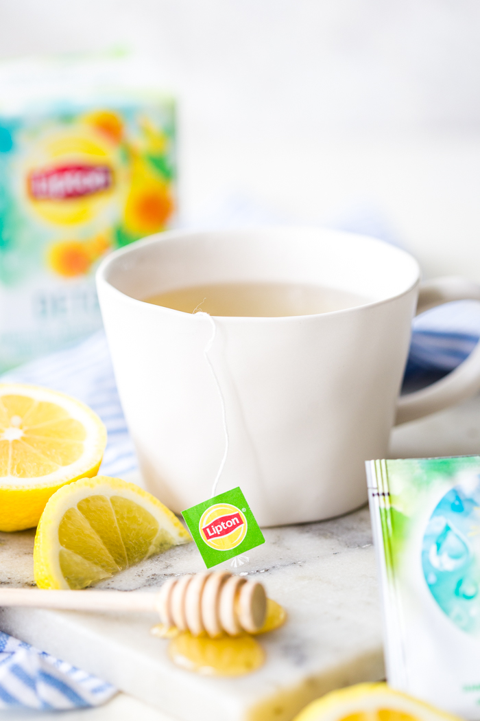 Letting your tea steep in a white mug with lemons