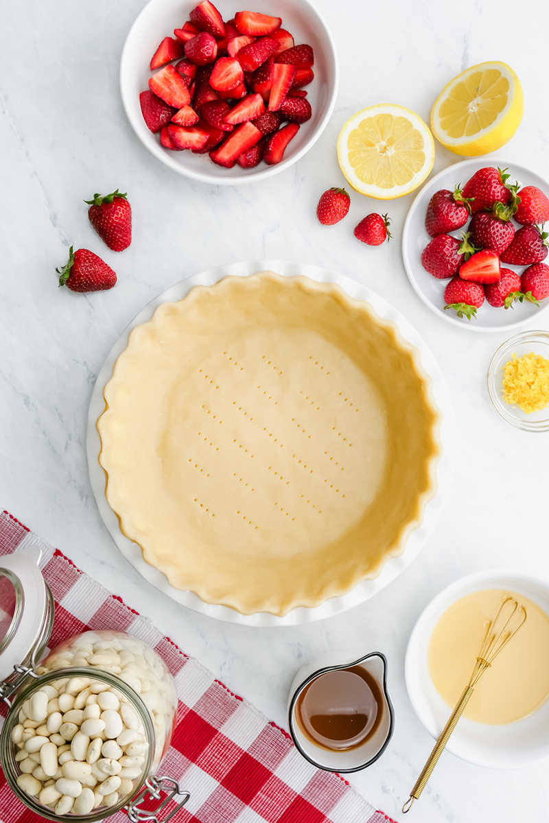 A top down shot of the ingredients for strawberry pie including a pre-baked crust