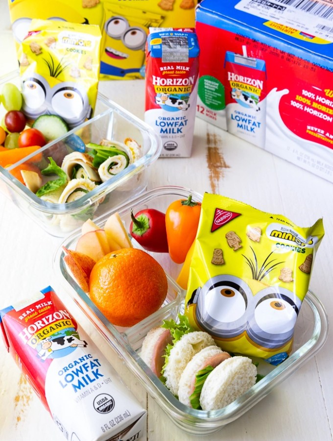glass bento box with mandarin orange, grape tomatoes, carrot sticks and celery sticks, a round sandwich and a yellow package of Nabisco minion cookies, packaging for horizon organic low fat milk boxes and Nabisco Minion cookies behind
