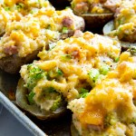 A sheet pan loaded with twice baked potatoes. Melted cheese on top, broccoli and ham pieces showing in the mashed potatoes.