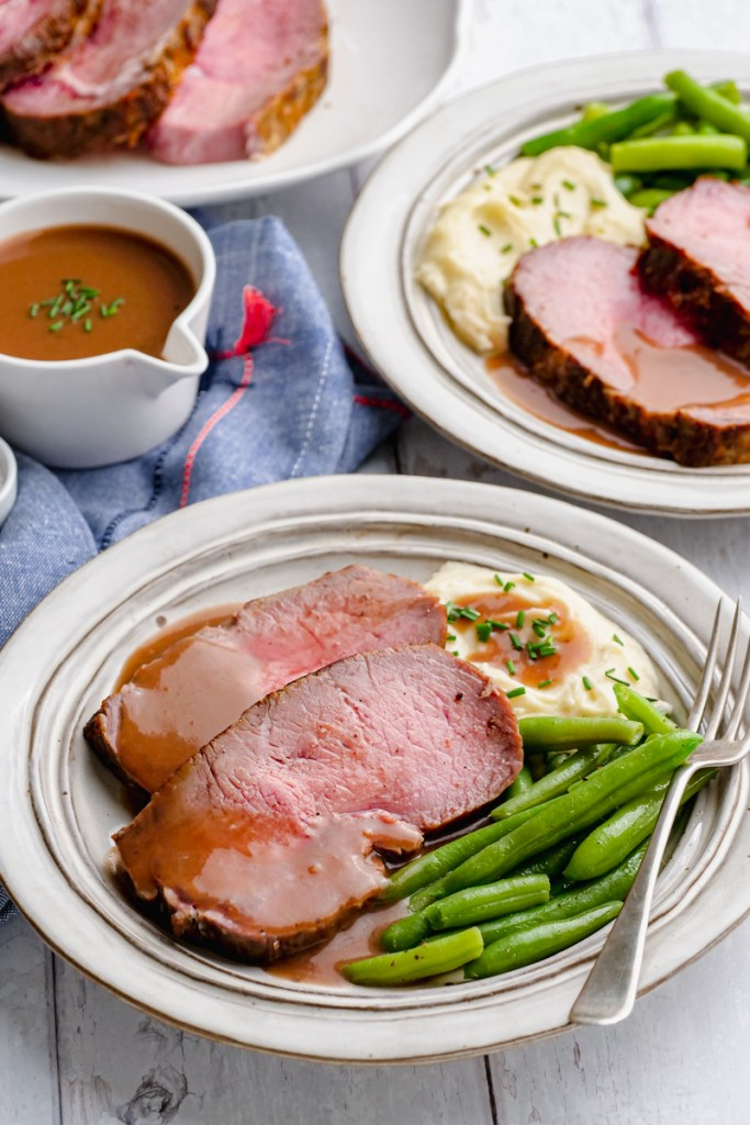classic roast beef with gravy in the background