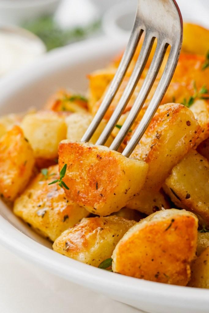 A fork poking into a crispy potato