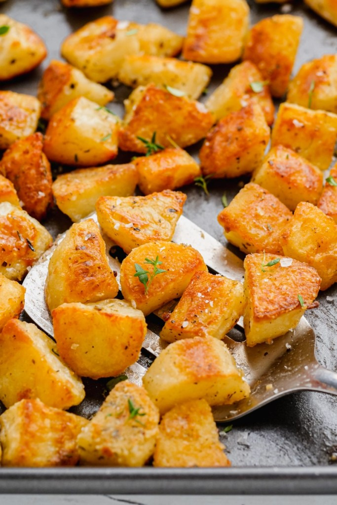 Crispy potatoes on a sheet pan with a metal spatula