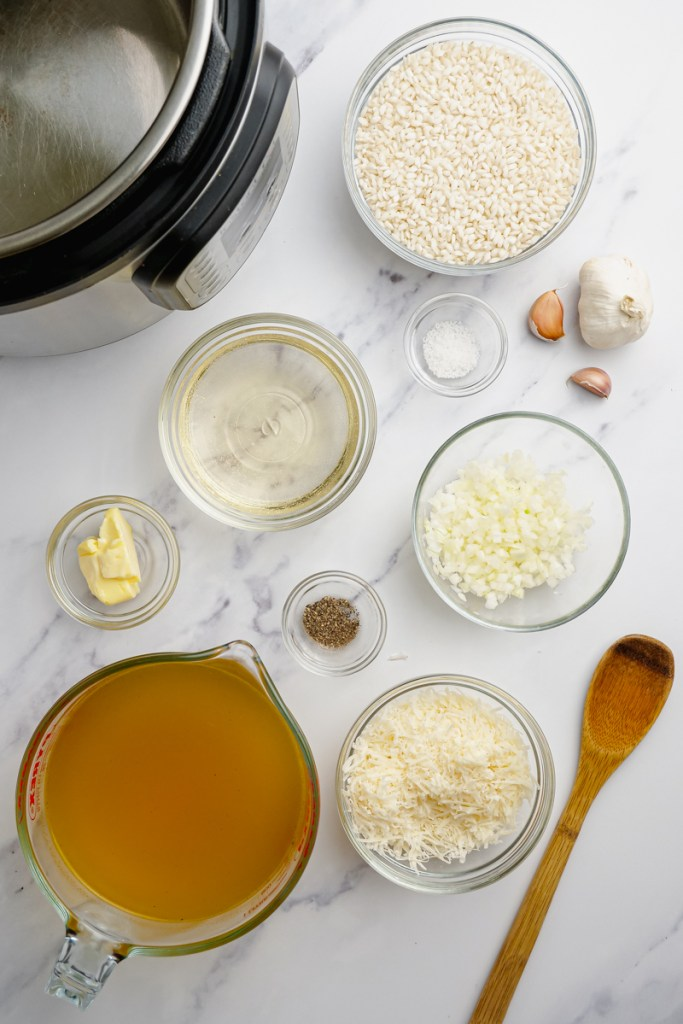 ingredients for parmesan risotto on counter with wooden spoon