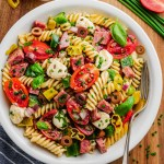 Italian pasta salad in white bowl with fork to the side