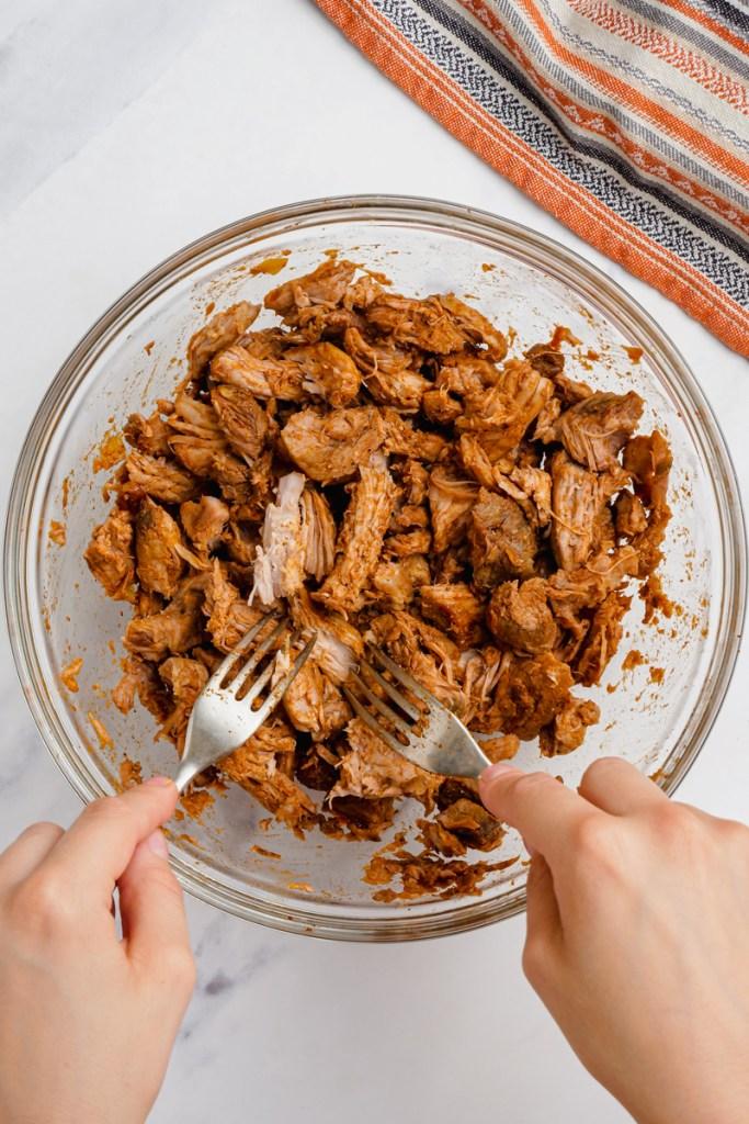 shredding pork for pork mole tacos