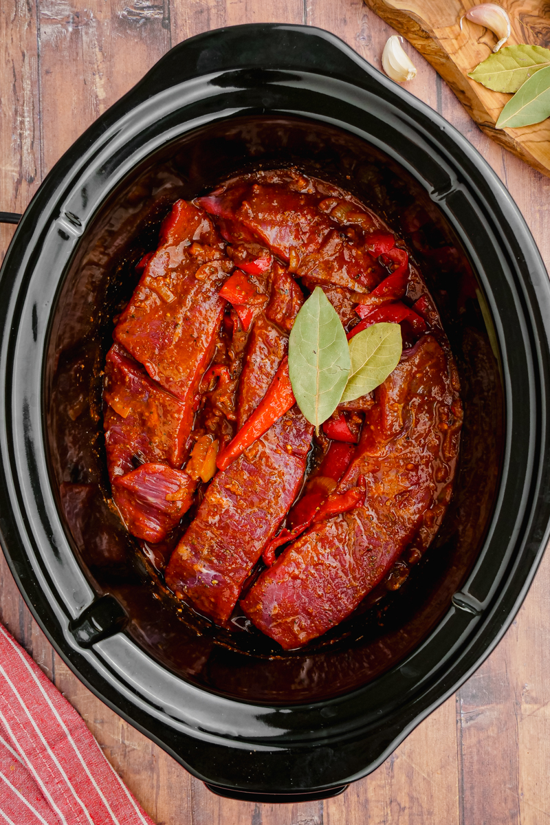 A black slow cooker with all the ingredients for ropa vieja inside, bay leaves on top.
