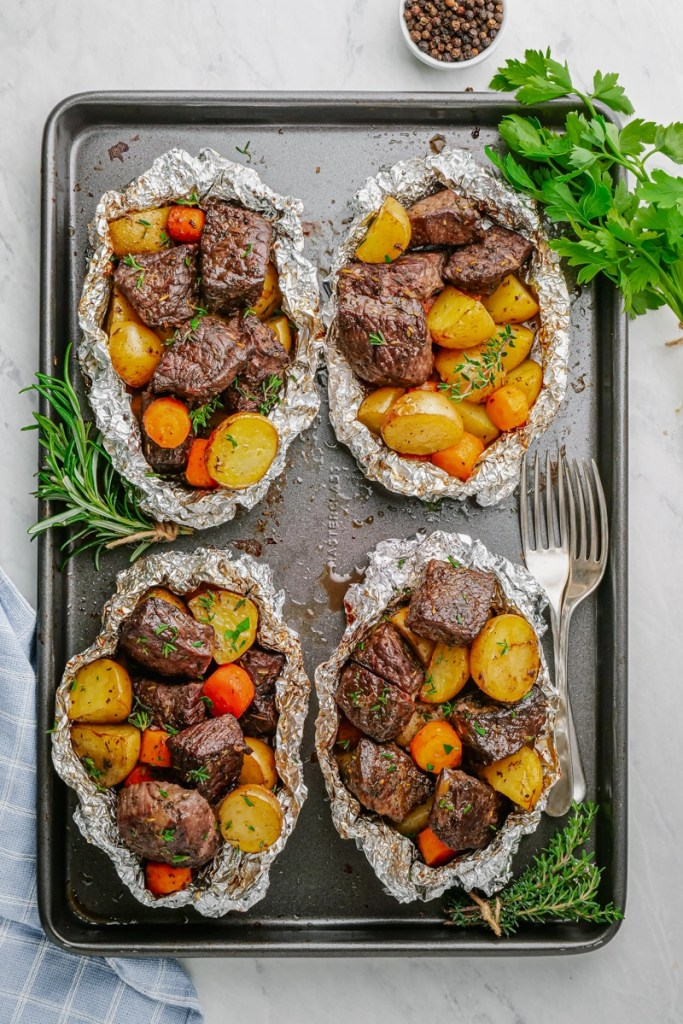 Steak and potato foil packs, 4 on a baking tray.