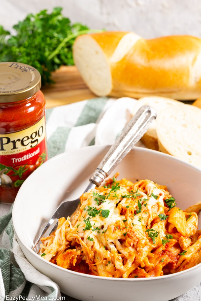 A white bowl with slow cooker chicken parmesan casserole in it, a bottle of Prego Sauce, and some french bread in the background.