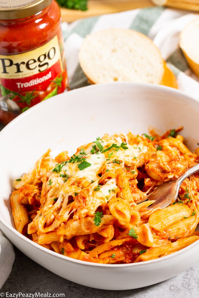 White bowl with penne and chicken parmesan made in the slow cooker
