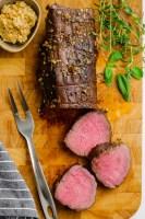 A half carved roast beef tenderloin on a cutting board